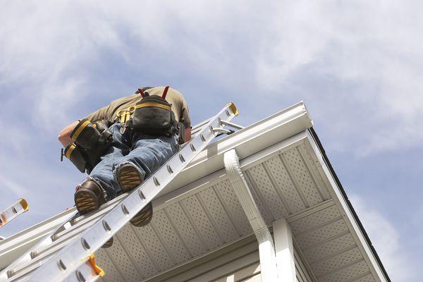 A handyman repairs his rain gutters