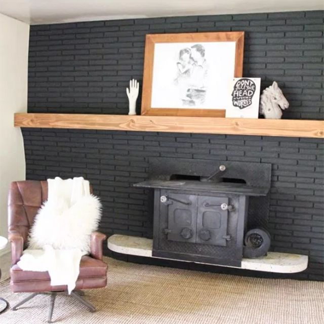 A living room with a wooden mantel on dark brick above a fireplace