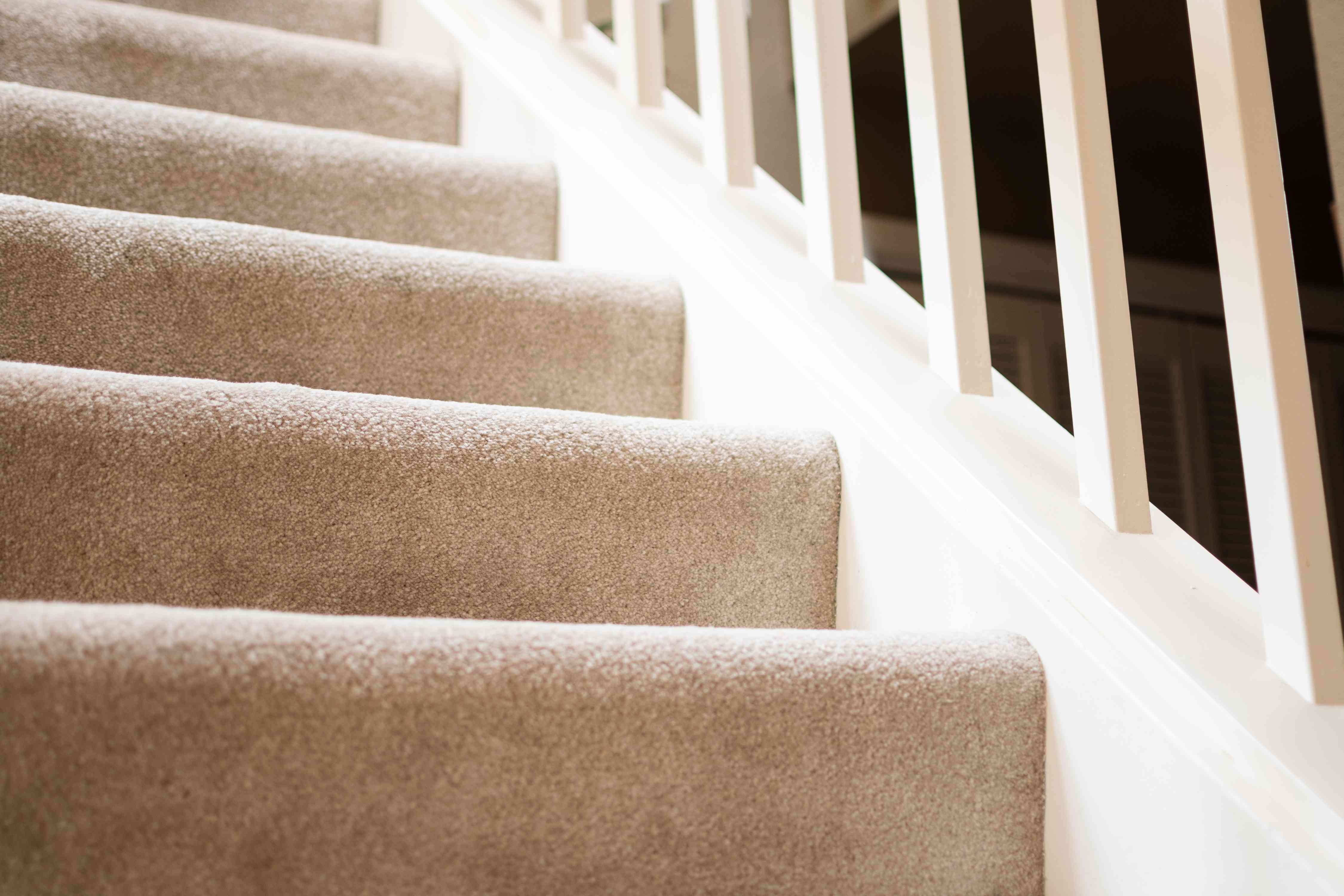 Tan carpeted stairs with white railing closeup