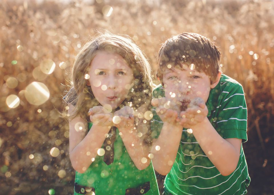 kids in green shirts blowing gold glitter