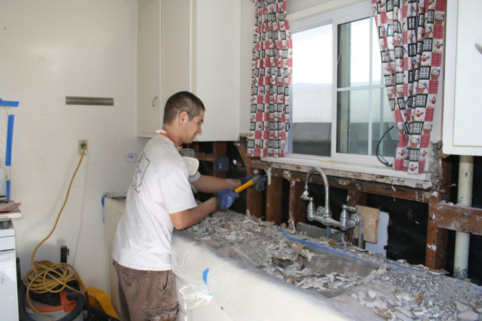 Worker demolishing a kitchen sink