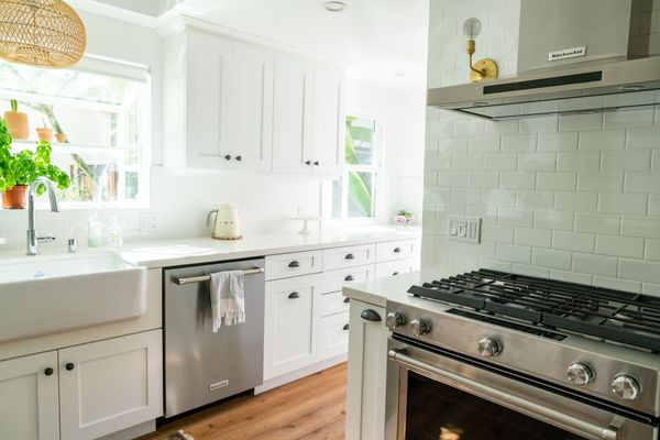 Natural light-filled kitchen with white cabinets, stainless steel appliances and mint green tiled walls