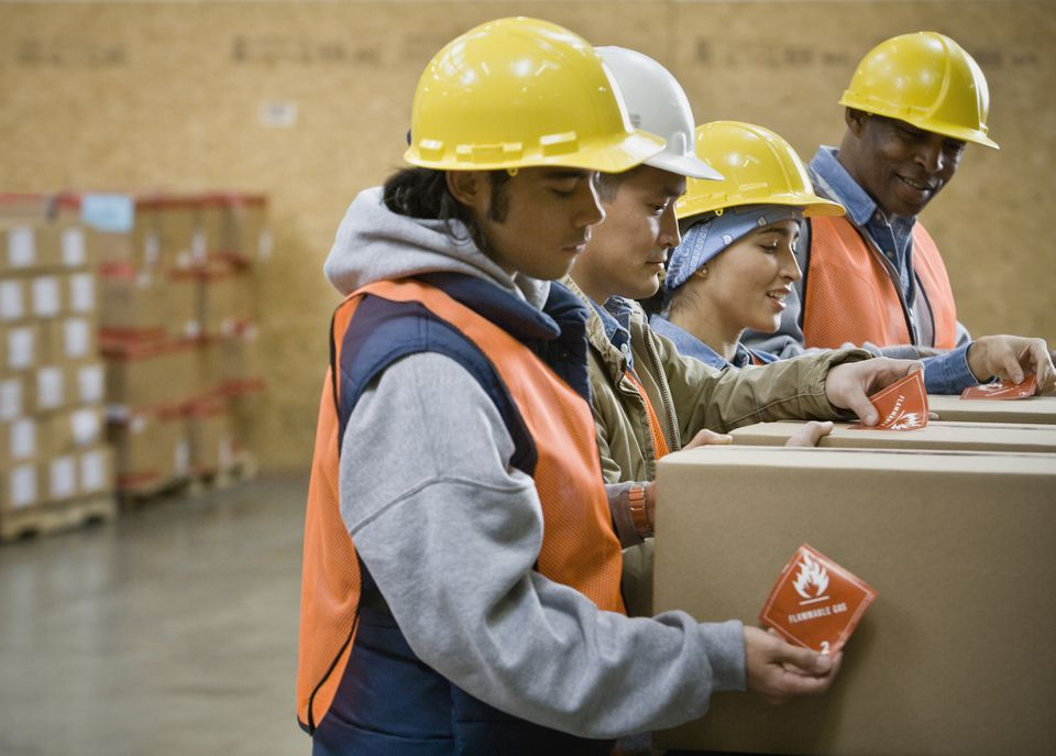 workers attaching labels to boxes