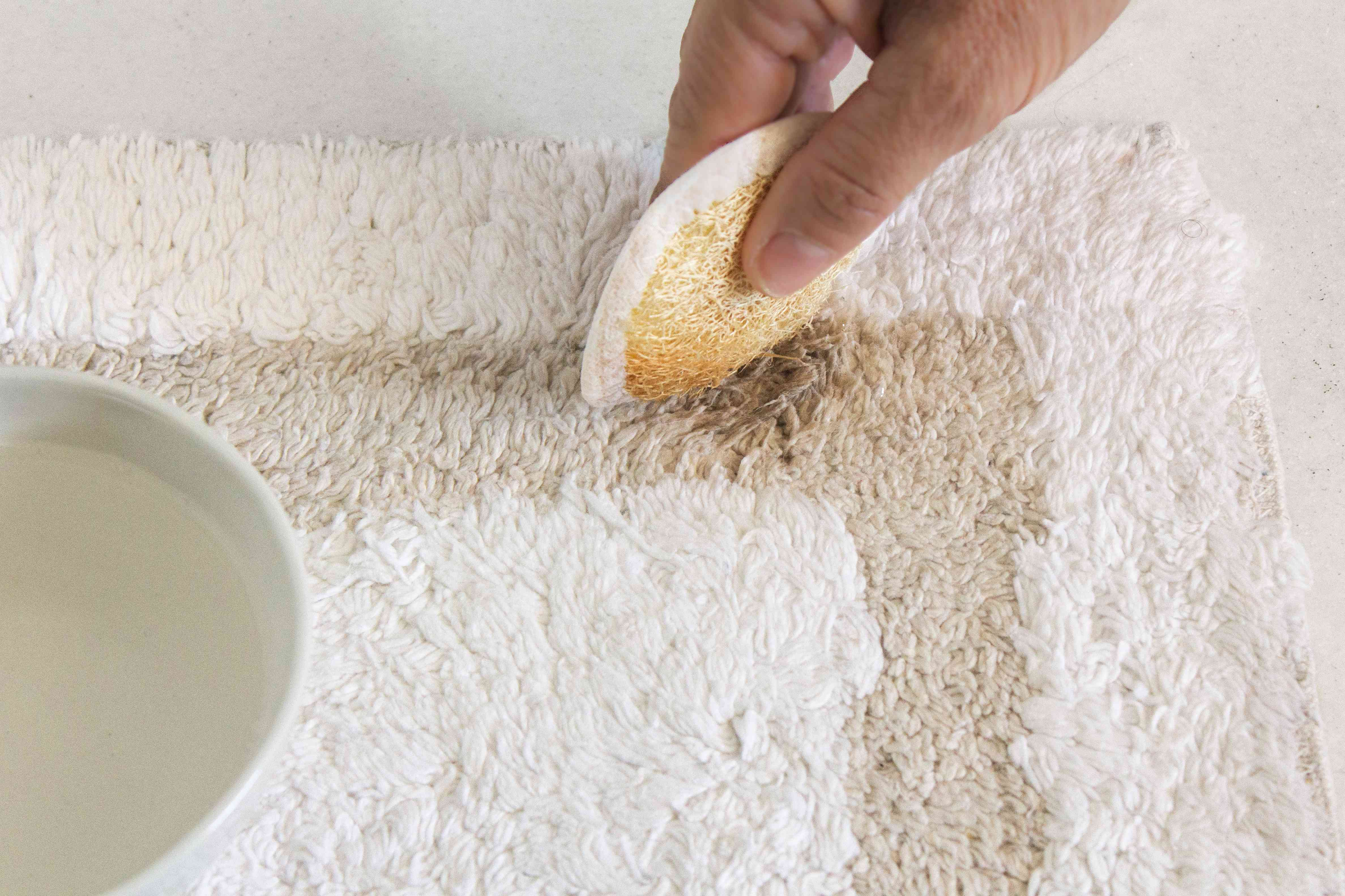 using a sponge on a stained bathroom rug