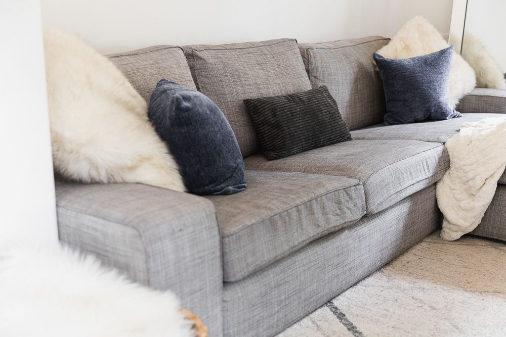 Old gray furniture covered with fluffy white, blue and black pillows to sell for cash