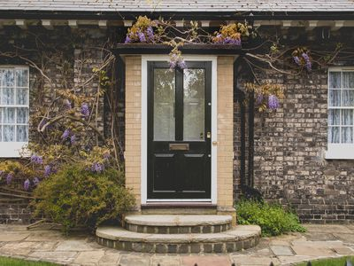 front door with purple flowers on a brick house
