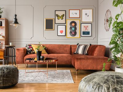 An orange sectional sofa in a colorful living room