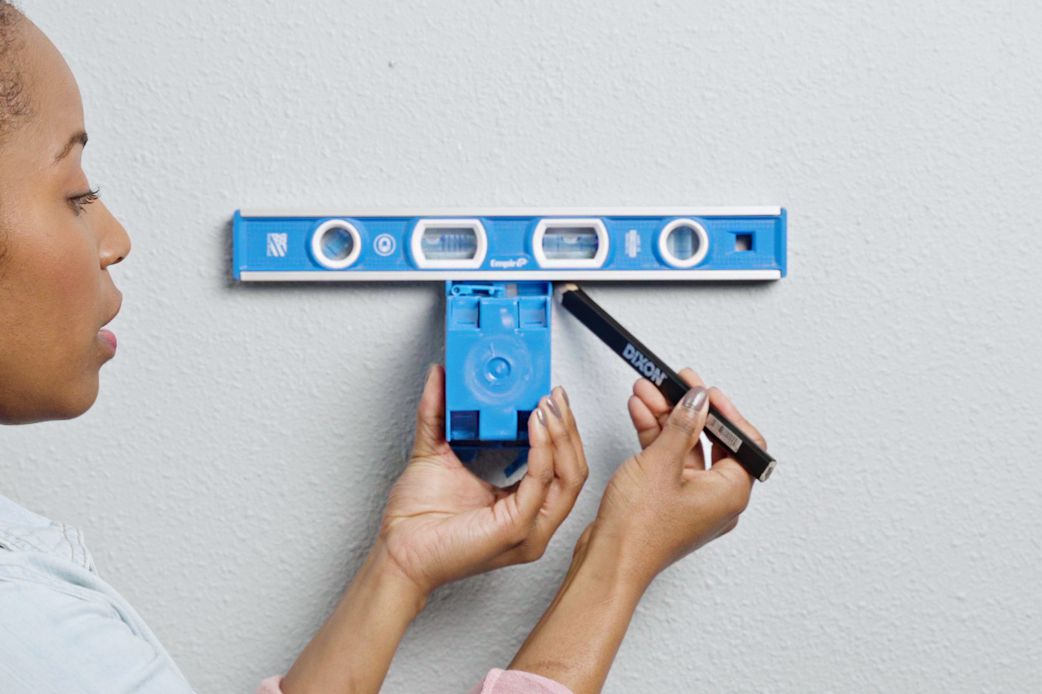 Preparing the wall cutout with blue old work (retrofit) electrical box and blue leveler