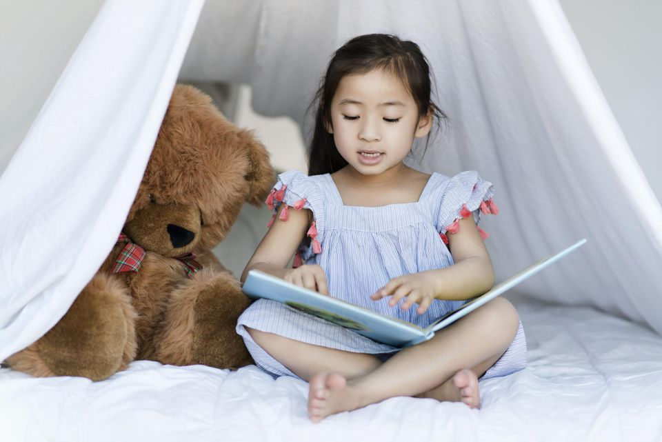 A girl reading in a white tent
