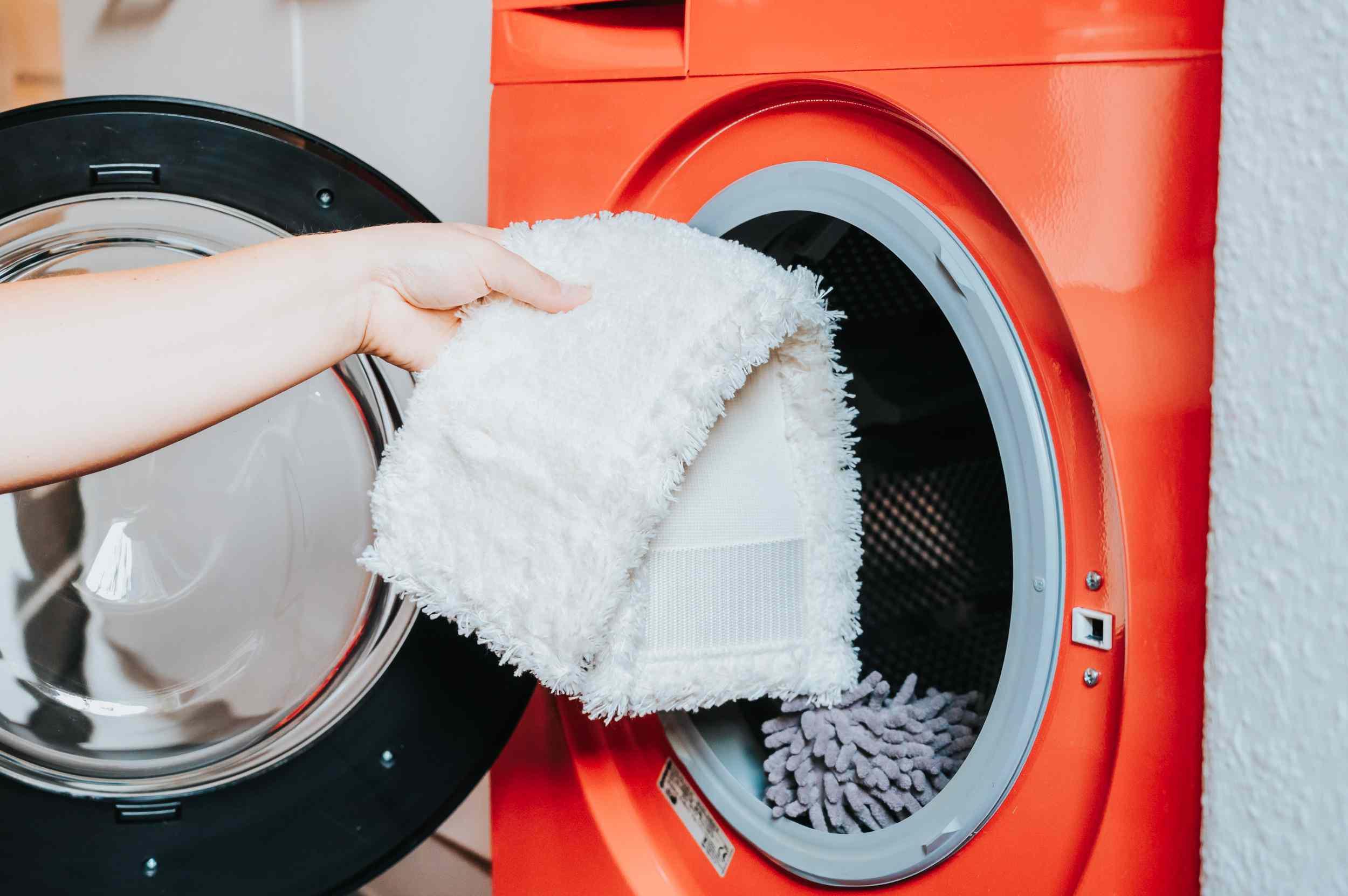 Removable white cotton mop head tossed in orange washing machine