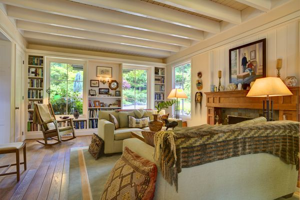 Country living room decor with rocking chair, fireplace, and couches.