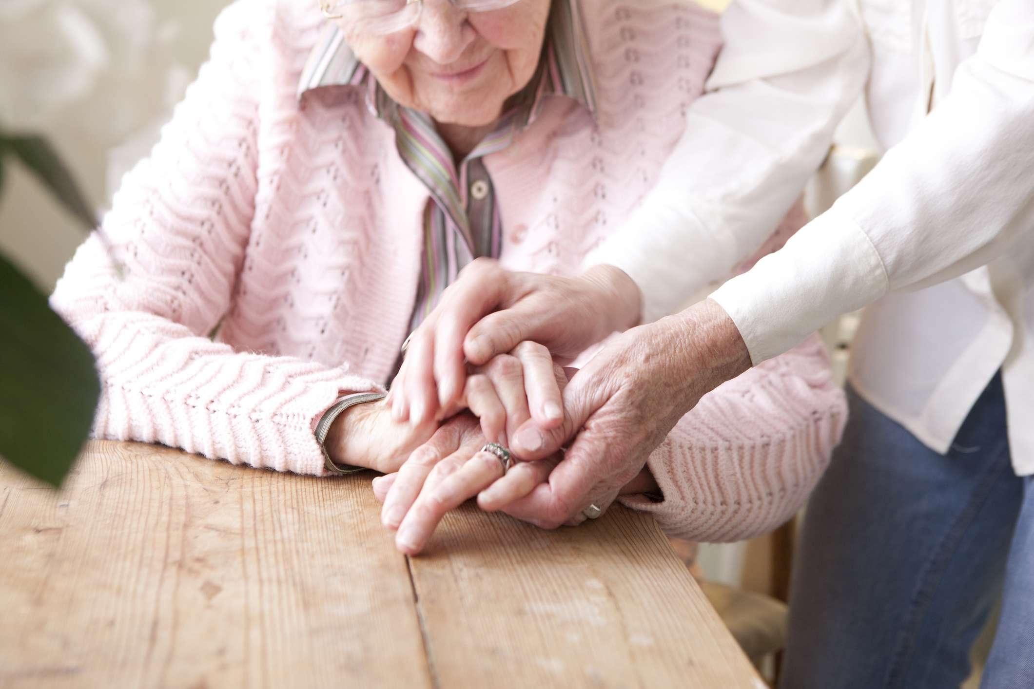 Senior parent and child holding hands