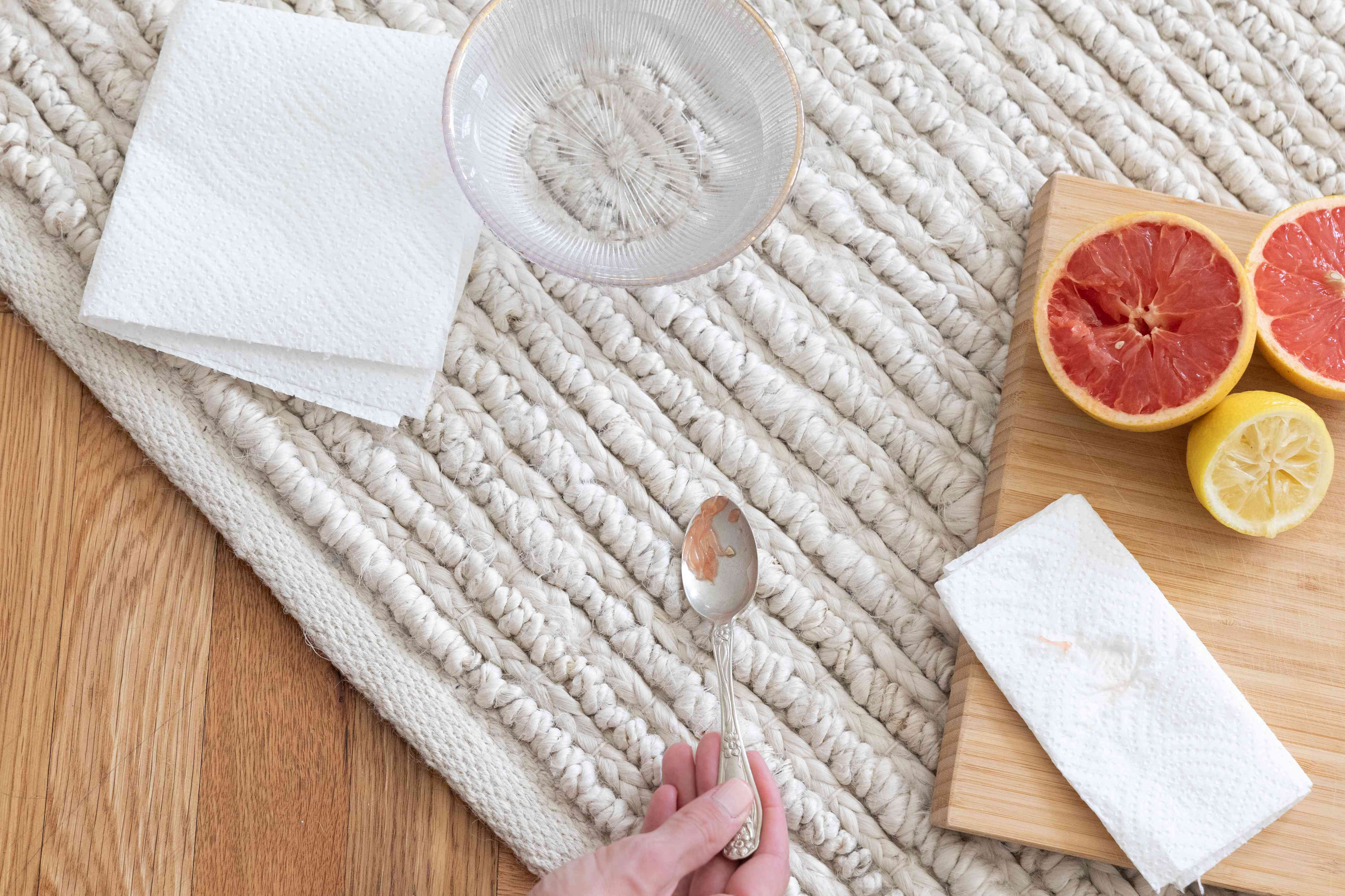 Citrus pulp solid removed from carpet with silver spoon next to folded paper towels and glass bowl