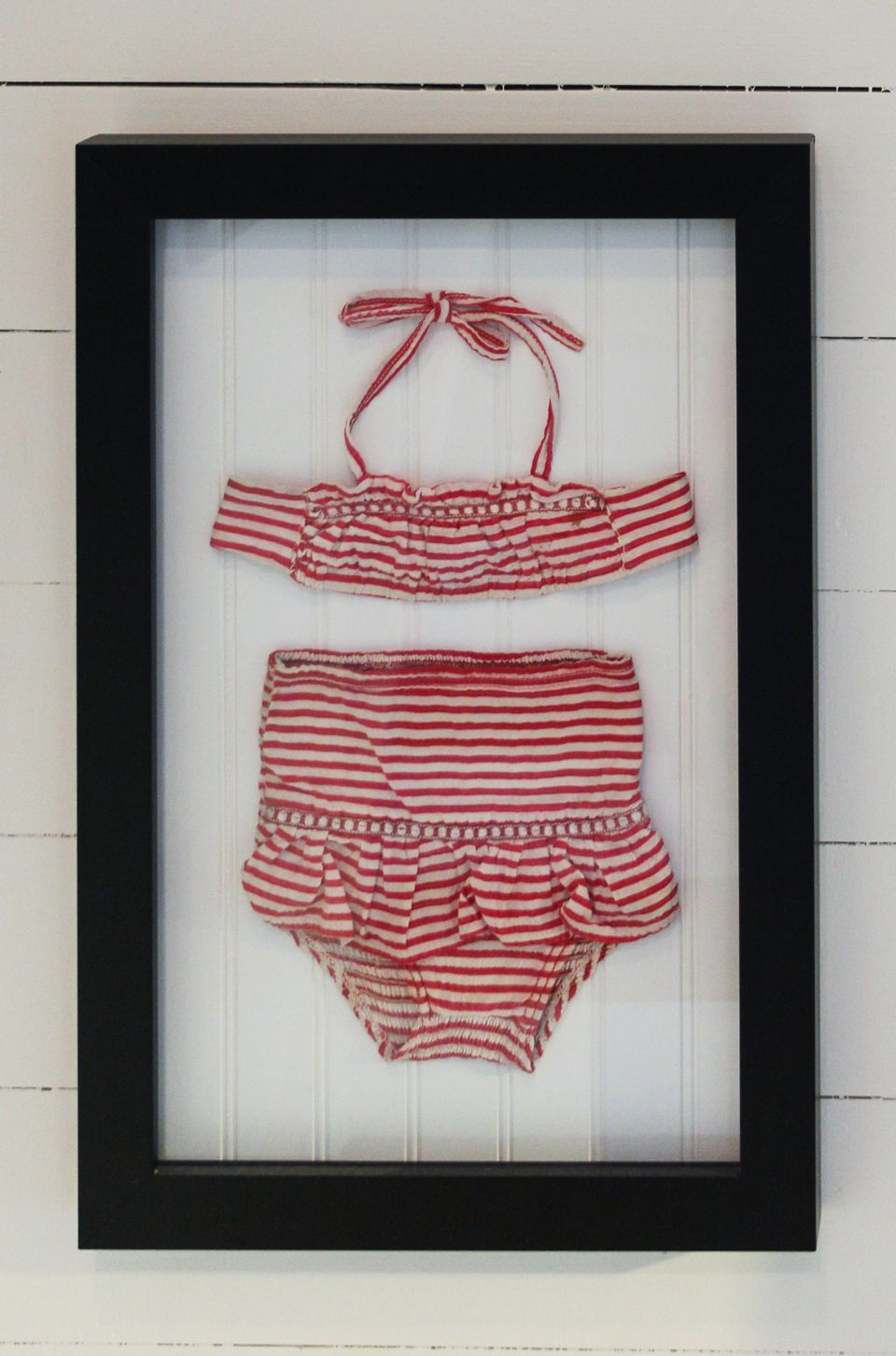 Vintage swimsuit framed and hanging on a wall