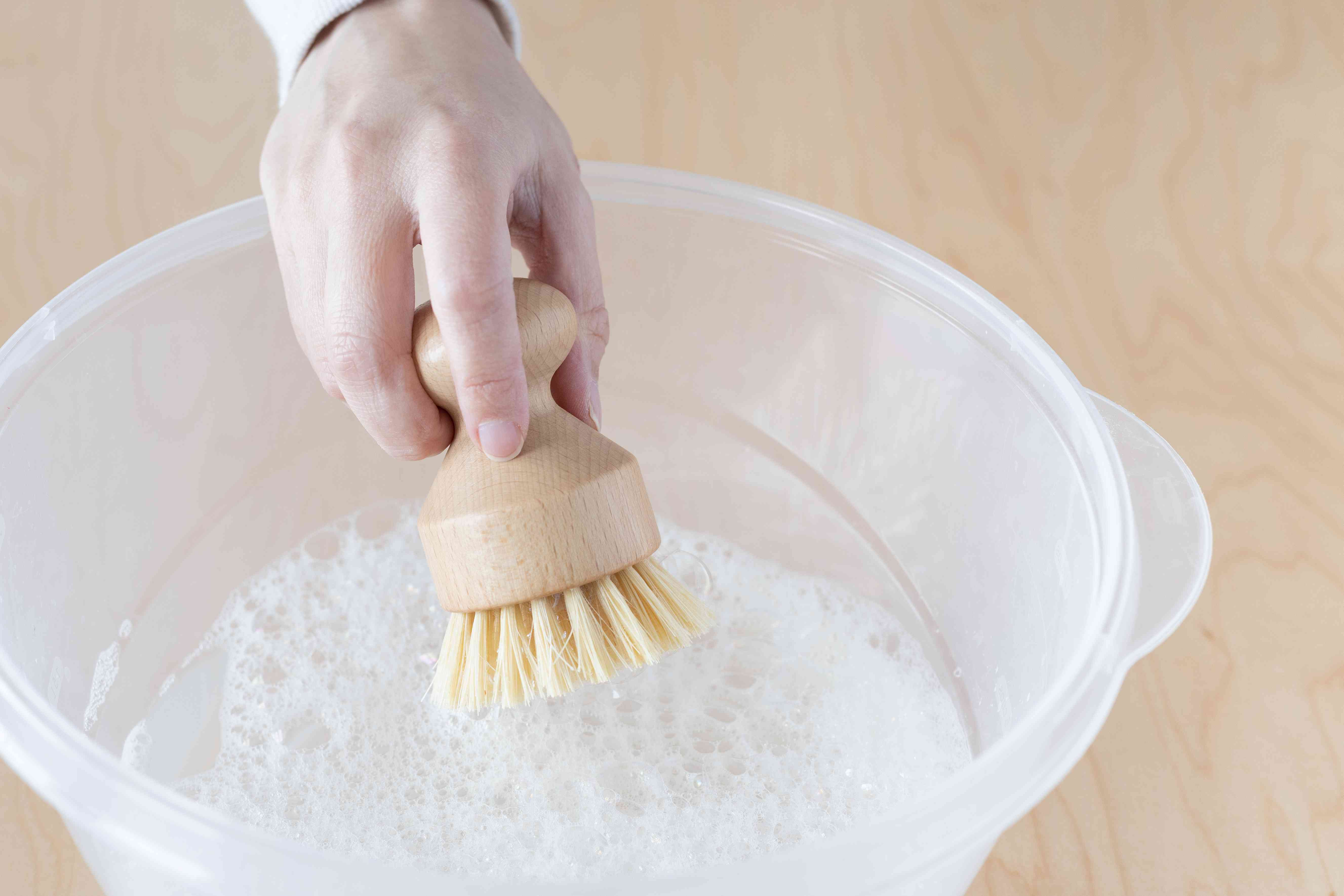 Soft bristled brush dipped into cleaning solution