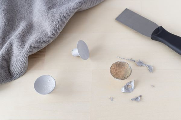 Paint removed from dresser knobs next to cloth and paint scraper
