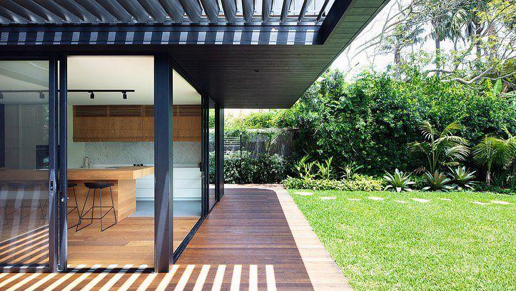 Casa con ventanas anchas y techo de listones de madera
