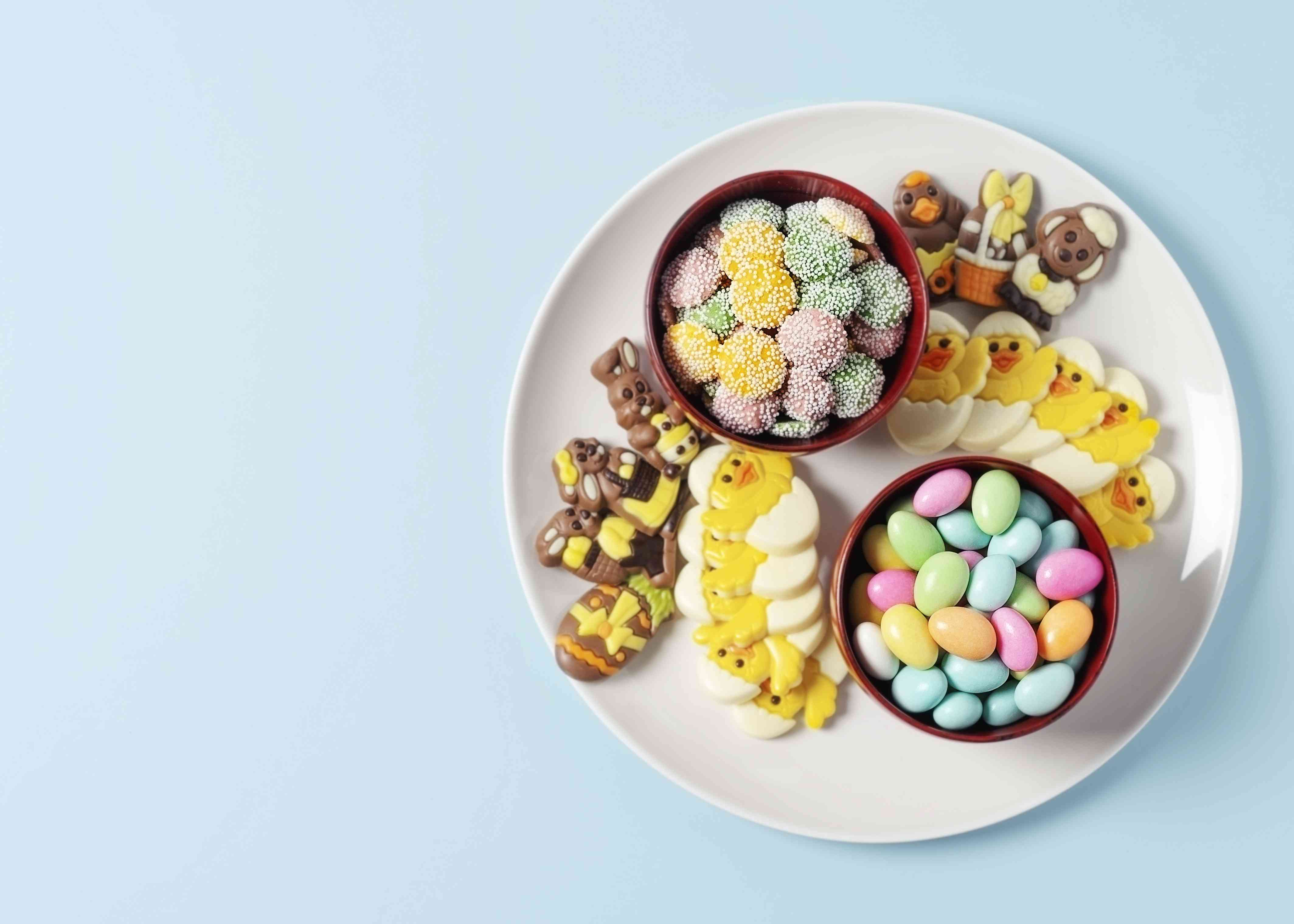 A variety of Easter chocolates and candy on a plate on blue background