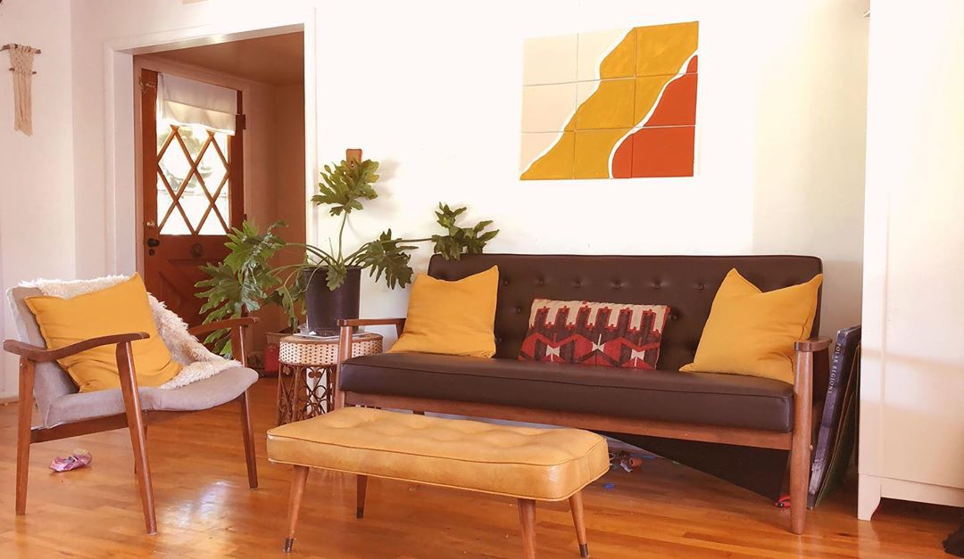 Sala de estar con sofá marrón y almohadas de mostaza