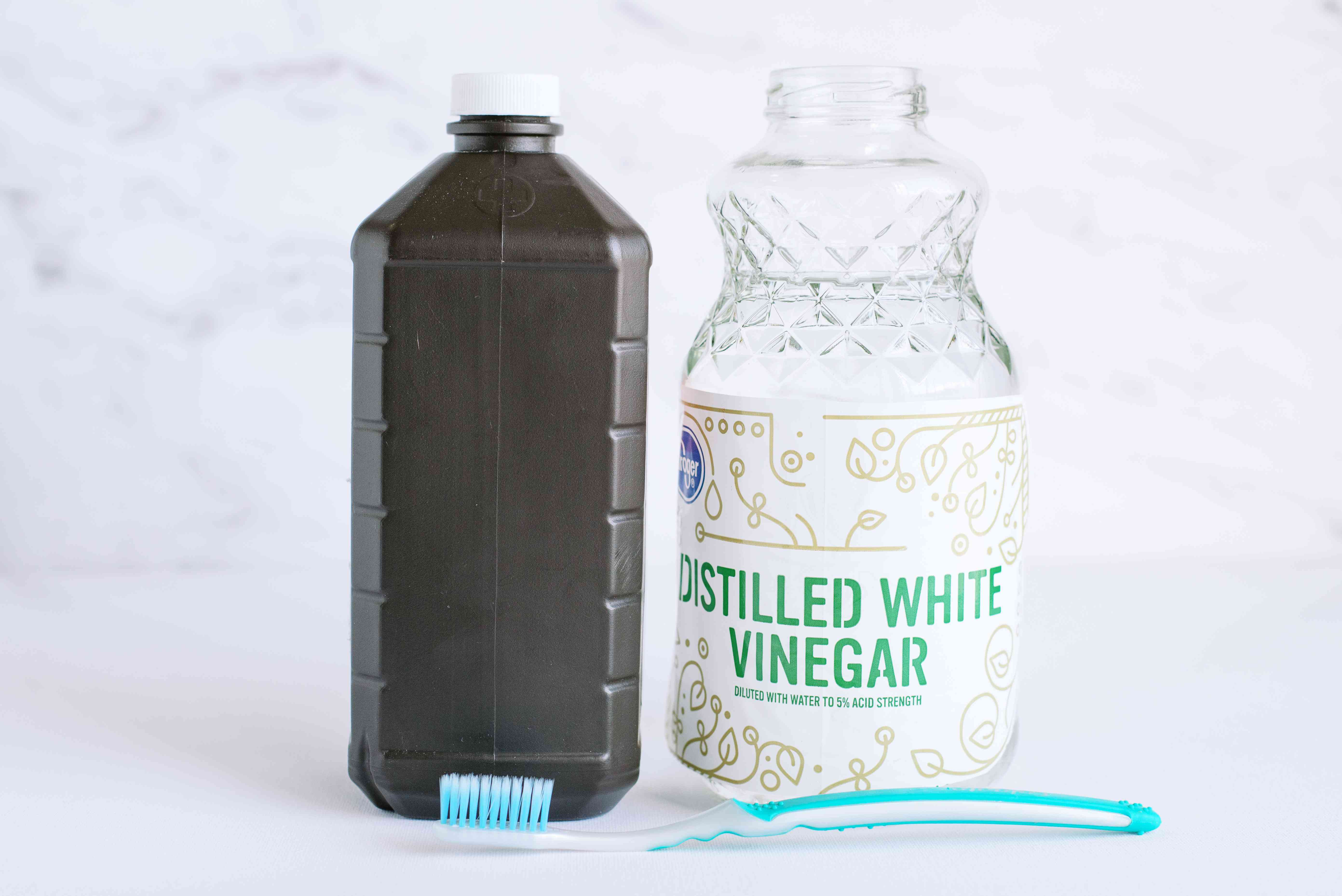 Brown bottle of hydrogen peroxide, glass container of distilled white vinegar and a toothbrush to clean portable humidifier