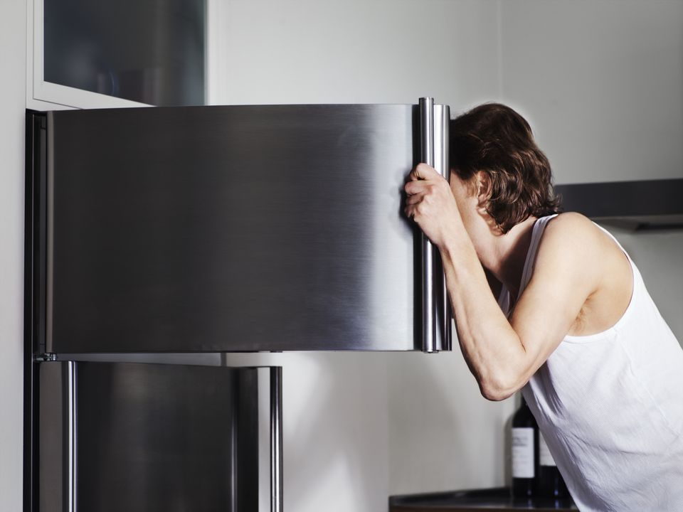 Man looking in freezer, face obscured by door, side view