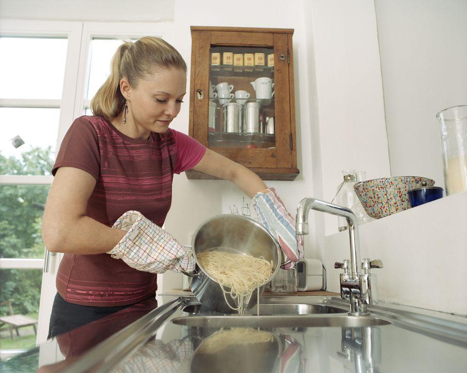 mujer vierte espagueti en el fregadero