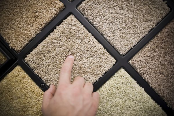 Finger pointing at one of several beige carpet samples on a carpet sample wall