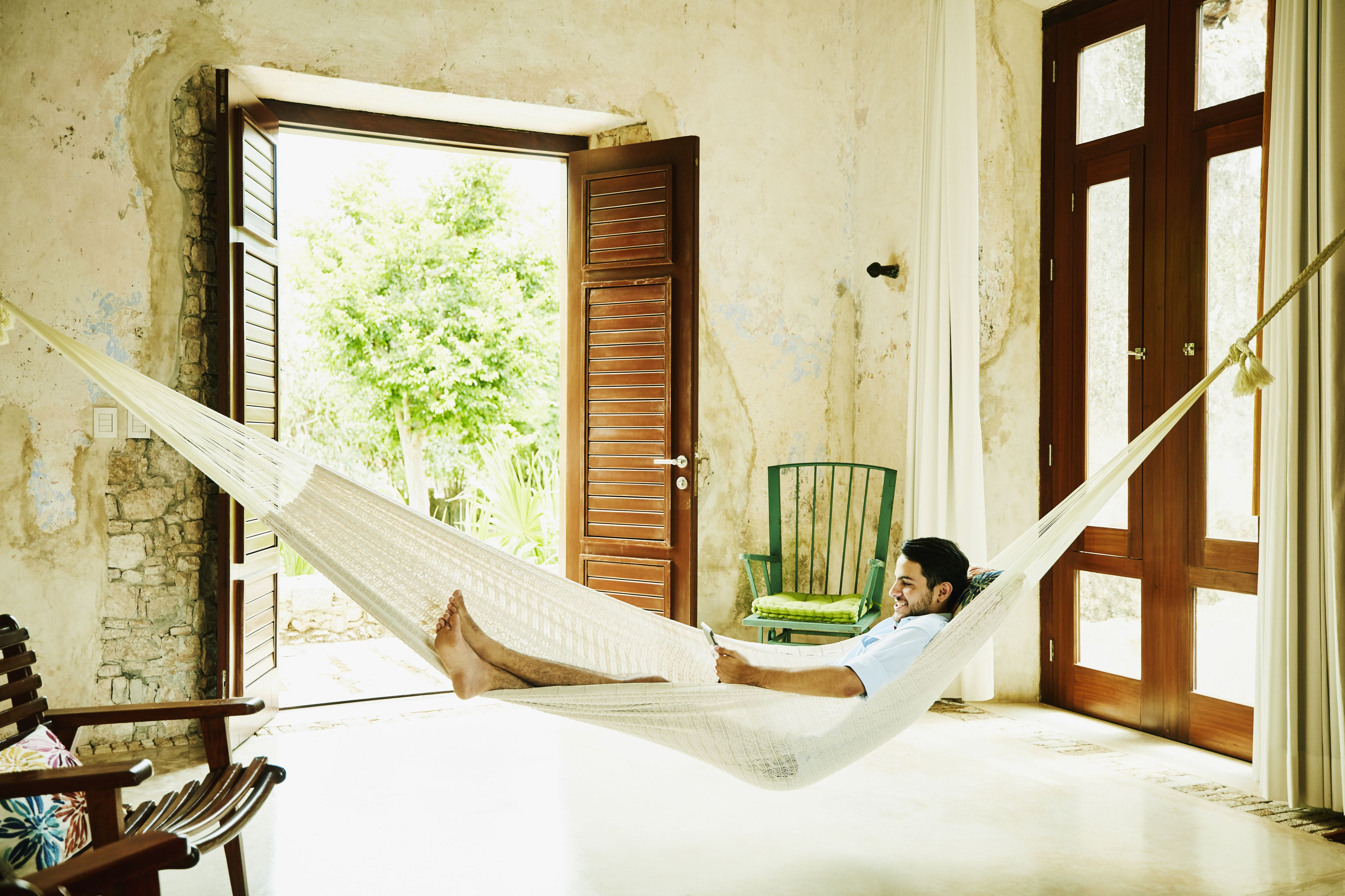 Smiling man relaxing in hammock in room at luxury resort reading digital tablet