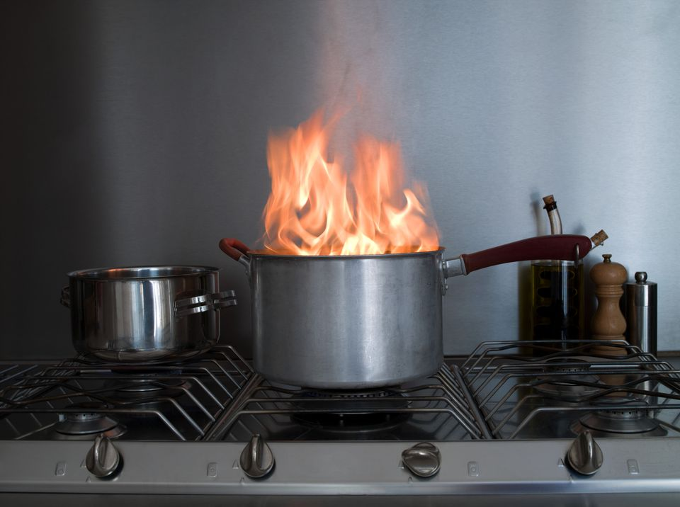 Pot on fire on a kitchen stove.