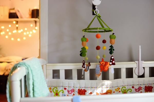 Сozy baby bed in the bedroom. Cosy white crib.
