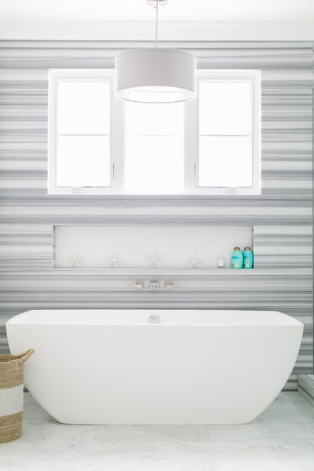 Grey and white bathroom with tub, window, and light.