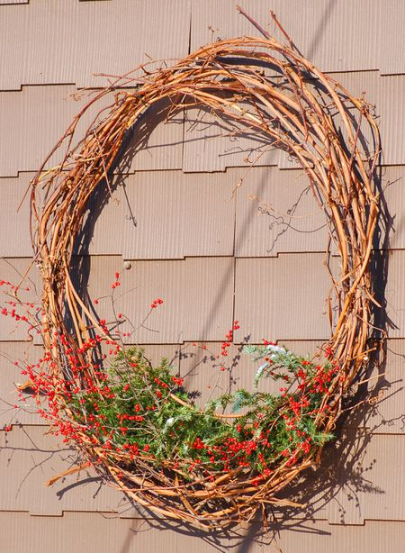 Photo: an idea for decorating a Christmas grapevine wreath. Insert greenery and berries.