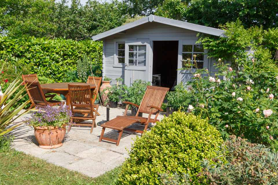 Garden shed with lounge chairs, a dining table, and lots of green shrubs.