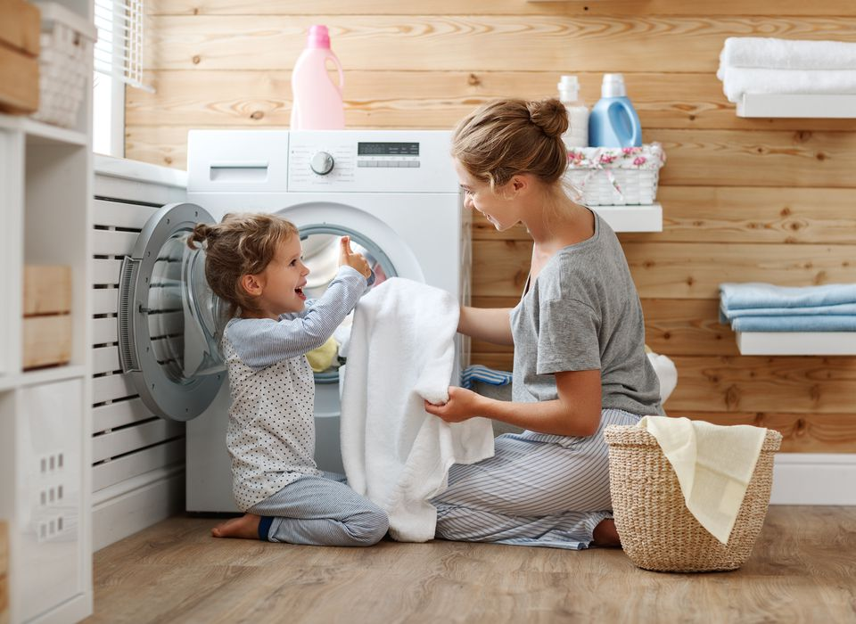 Happy family laundry chores, as mother and kid laugh by the washer