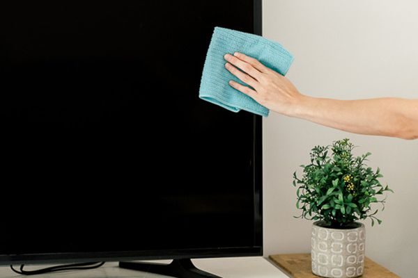 person cleaning a tv screen