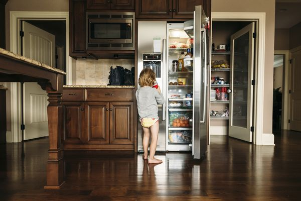 Boy drinking while standing by refrigerator in kitchen at home - stock photo