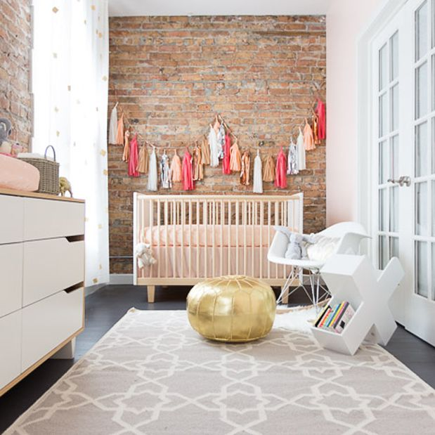 Simple nursery with neutral colors and beautiful exposed-brick walls.