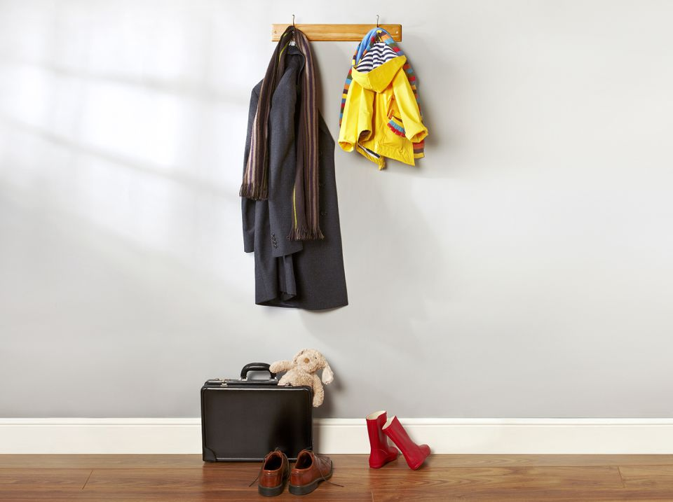 two rain coats hanging up on hooks with various shoes and objects beneath them