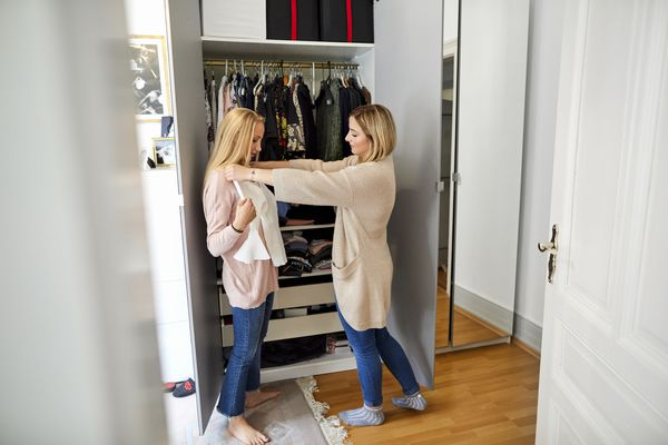 Two young women at wardrobe choosing clothes