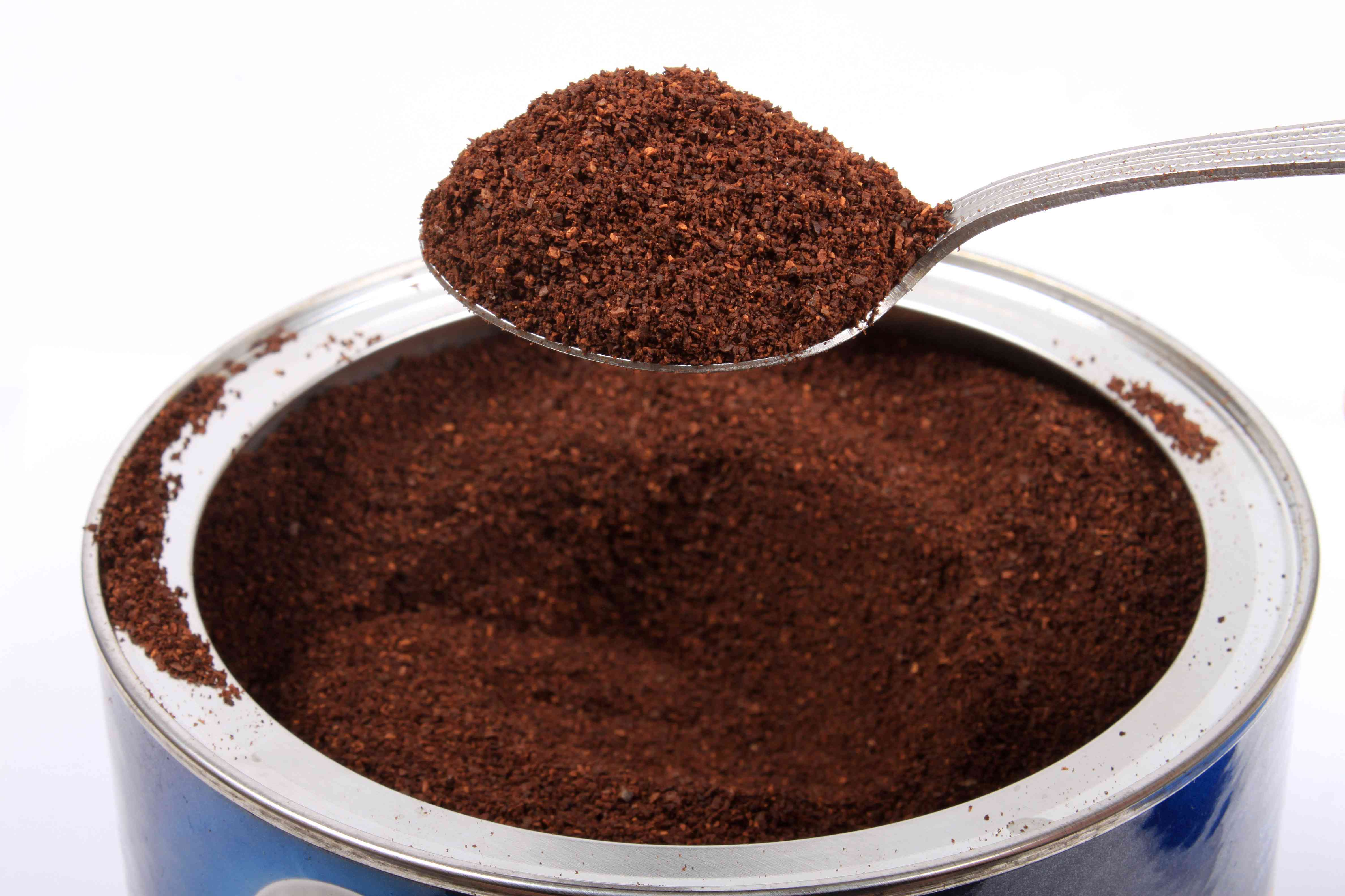 Spoonful of coffee grounds above a blue coffee can