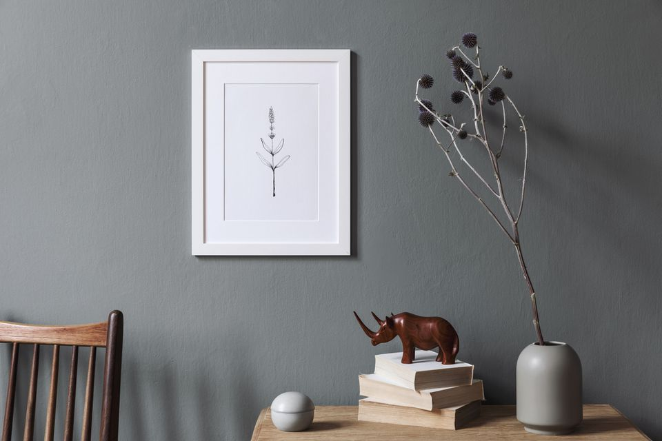 Design interior of living room at modern apartment with white mock up photo frame, wooden shelf, stylish chair, vase with flower, books, sculpture and elegant accessories. Stylish home decor, Template