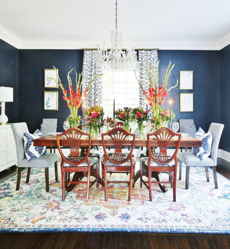 Dining room with dark blue walls and large bouquets of flowers on the table.