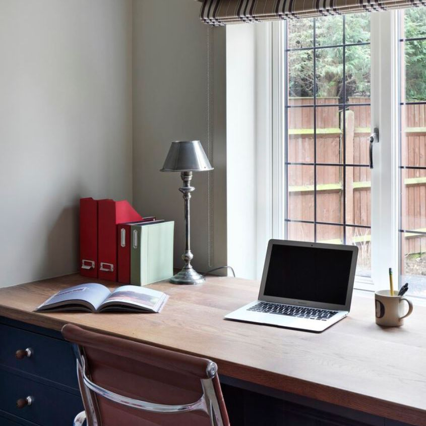 Home office with desk up against large window