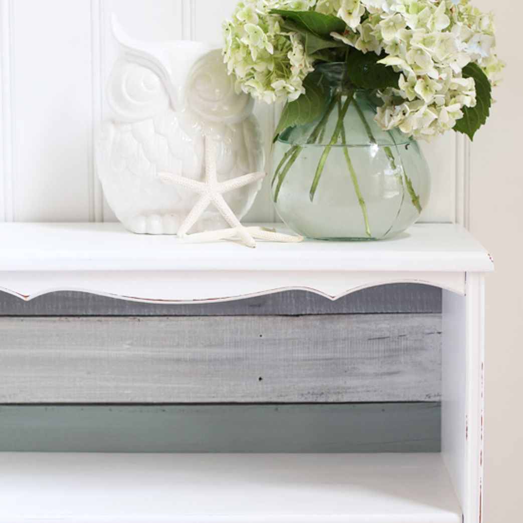 DIY bookcase back made from repurposed fence pickets and a vase of white flowers on top.