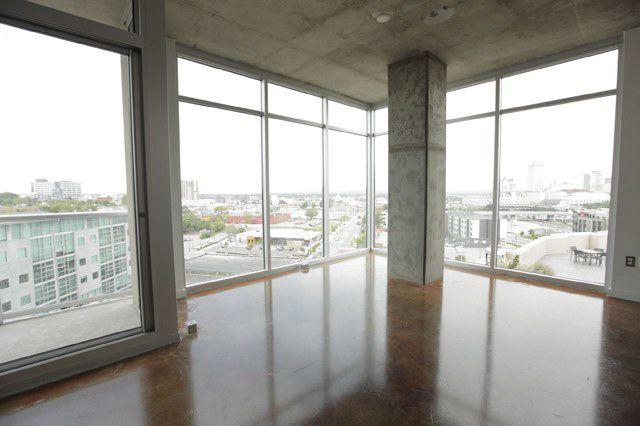 pisos tipo loft de concreto con ventanas de piso a techo con vista a los edificios