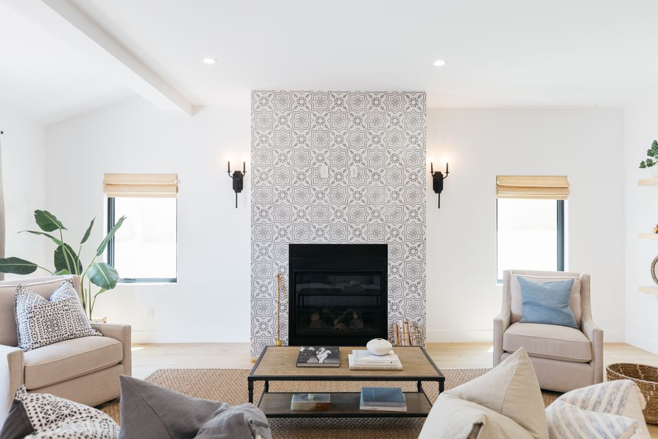 Gray and white patterned tile fireplace in middle of brightly-lit and decorated living room