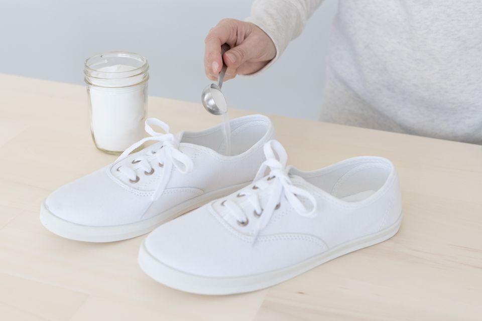 Baking soda being poured into white canvas shoes