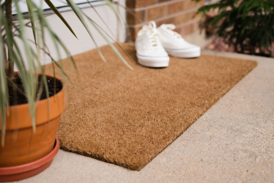 Brown doormat with white shoes on top and behind houseplant