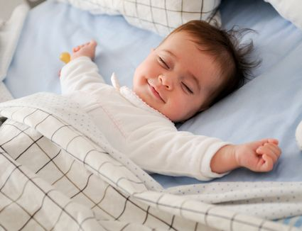 High Angle View Of Baby Sleeping On Bed At Home