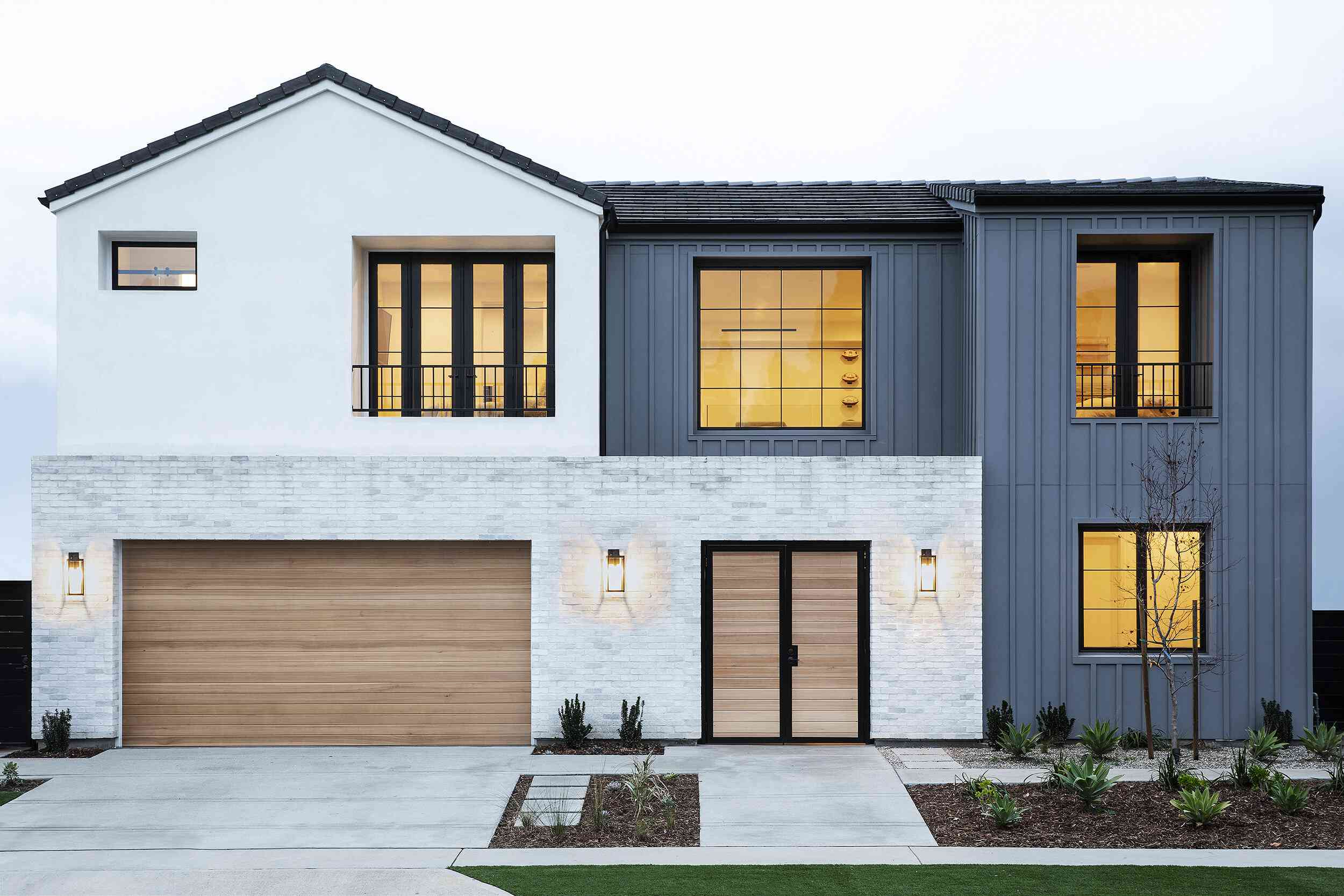 house with white brick and blue exterior, wooden garage door